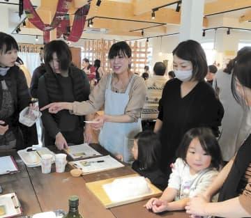 大勢の母子でにぎわうママフェスで、パンの焼き方を教える佐藤さん(中央)