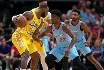 The Los Angeles Lakers' LeBron James (23) works against the Miami Heat's Jimmy Butler (22) in the first quarter at the AmericanAirlines Arena in Miami on December 13, 2019. - DAVID SANTIAGO/Miami Herald/TNS