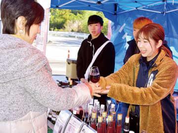 ワインを受け取る来場者(左)=14日午前11時20分ごろ、秩父市下吉田の釜の上農園村