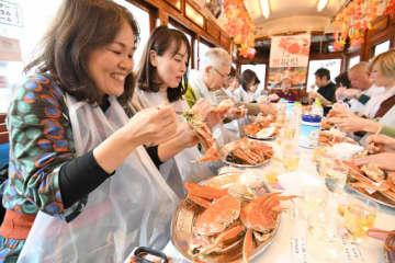 路面電車の中で旬の松葉ガニを味わう参加者=14日、大阪市内