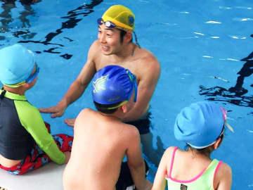 ベトナムの子どもたちに正しい泳ぎ方を丁寧に教える鮎澤さん=ベトナム・ハノイ(鮎澤さん提供)