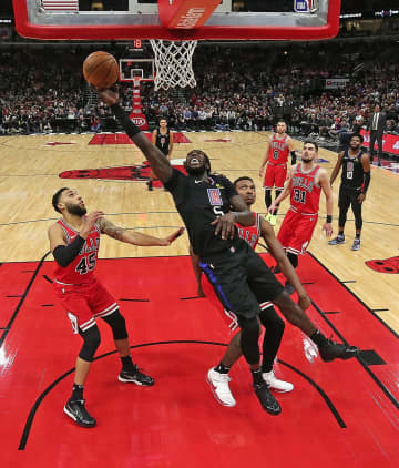 Montrezl Harrell #5 of the LA Clippers lays in a shot between Denzel Valentine #45 and Wendell Carter Jr. #34 of the Chicago Bulls at the United Center on December 14, 2019 in Chicago, Ill. - Jonathan Daniel/Getty Images North America/TNS