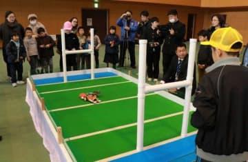 コートに向かい合い自作ロボットの性能を競う出場者ら