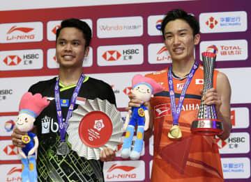 バドミントンのワールドツアー・ファイナル男子シングルスで優勝し、笑顔の桃田賢斗。左は2位のギンティン=15日、中国・広州(共同)