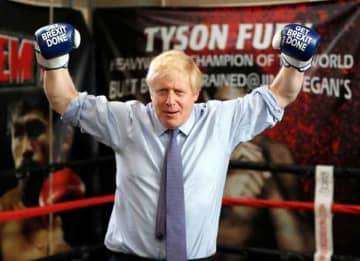 "MANCHESTER, ENGLAND - NOVEMBER 19: Britain's Prime Minister Boris Johnson poses for a photo wearing boxing gloves emblazoned with ""Get Brexit Done"" during a stop in his General Election Campaign trail at Jimmy Egan's Boxing Academy on November..."