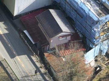 小川和男さんの自宅。手前が住宅の裏側。奥の白っぽい建物に面して玄関がある=14日、東京都青梅市(共同通信社ヘリから)