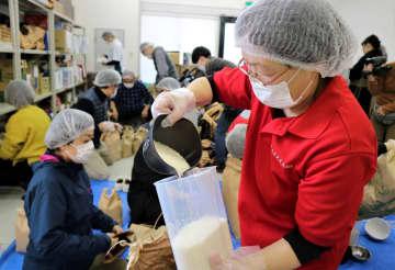 米を小分けにするスタッフ=長崎市中町、つなぐBANK倉庫