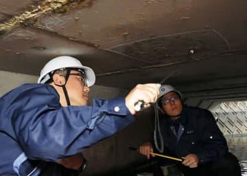 専用の道具を使って橋の点検をする玉名市職員の木下義昭さん(左)=玉名市