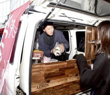出来たてのおにぎりを販売する原田健太郎さん(左)=12月12日、福井県永平寺町の福井県立大学永平寺キャンパス