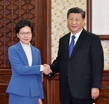 中国の習近平国家主席(右)と握手する香港政府トップの林鄭月娥行政長官=16日、北京(香港政府提供・共同)