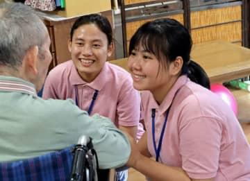 施設利用者(左)と笑顔で触れ合うミャンマー人の技能実習生=長崎市油木町、特別養護老人ホーム・サンハイツ