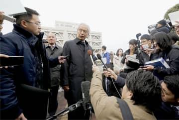 東京電力福島第1原発事故で自主避難した住民らの訴訟の判決を受け、記者の質問に答える原告側弁護士(中央)=17日午前、山形地裁前