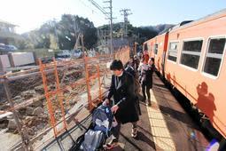 工事が進む新駅舎(左奥)と、野ざらしとなったホームを利用する観光客=JR柴山駅