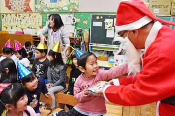 園児に絵本のクリスマスプレゼントを贈る松永一広さん(右)=伊万里市の黒川幼稚園