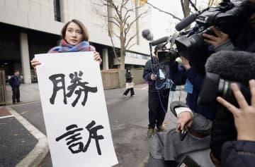 性暴力被害を巡る訴訟の判決後、東京地裁前で「勝訴」と書かれた紙を掲げるジャーナリストの伊藤詩織さん=18日午前