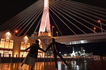 「プロポーズの聖地」に認定された青森市のベイエリア。美しい夜景の前でポーズをとってくれる外国人カップルも=17日午後7時20分ごろ