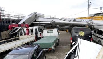 クレーン車が倒れ、車が下敷きになる事故があった現場=18日午前11時11分、宮城県塩釜市