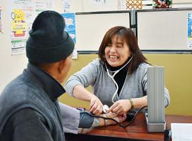 買い物客の血圧を測る白鳥ハイツ職員