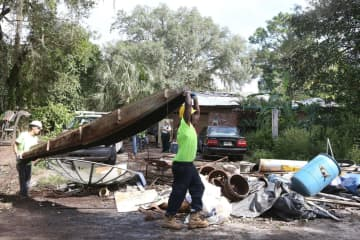 Workers haul off junk which has accumulated over the years at the home of Alan Davis in Altamonte Springs, Fla. The Seminole Sheriff's office supervised the removal on September 3, 2015. - George Skene/Orlando Sentinel/TNS
