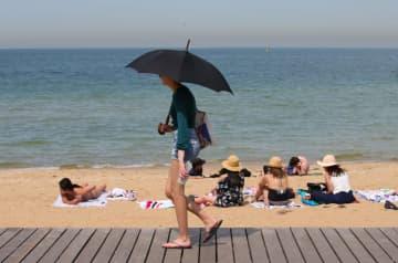 18日、オーストラリア・メルボルン近くのビーチに集まる人たち(ロイター=共同)