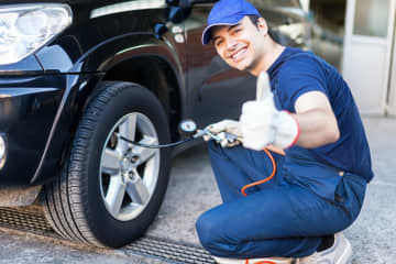 Why is this man happy? Because he's charging you 30 bucks apiece to fill your tires with nitrogen. - Dreamstime/Chicago Tribune/TNS