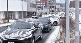 スピードを落として走る車で混み合う道路=20日午前8時ごろ、室蘭市中島町