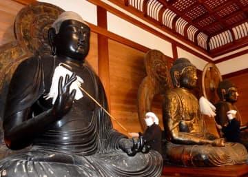 長い柄の付いたはたきを使い、丈六仏に積もったすすを慎重に払う僧侶=中尊寺讃衡蔵
