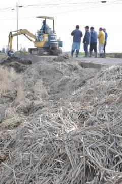 農地に堆積した稲わらの除去作業を進める農家ら=水戸市島田町