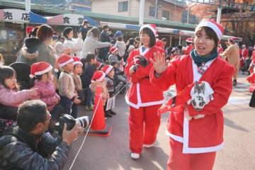 サンタクロースの衣装をまとい、パレードする飼育員とウサギたち