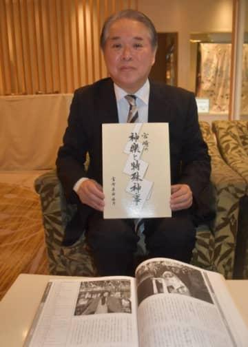 県神社庁が発行した書籍「宮崎の神楽と特殊神事」を手にする玉置徳行さん=宮崎市・宮崎神宮会館