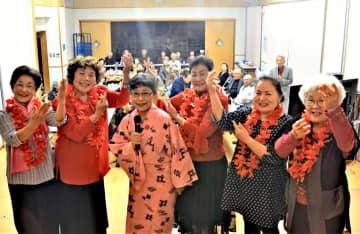 ダンサーを従えて「島のブルース」を歌った天久静子さん(中央)=15日、宜野湾市の上大謝名区公民館