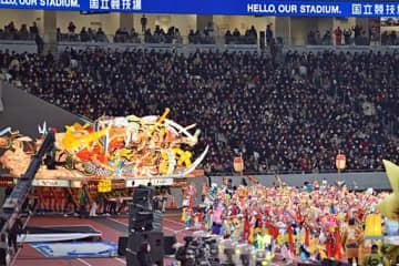 明かりが入った大型ねぶたの前で、大観衆に乱舞を披露するハネトたち=21日午後7時20分ごろ、東京の国立競技場