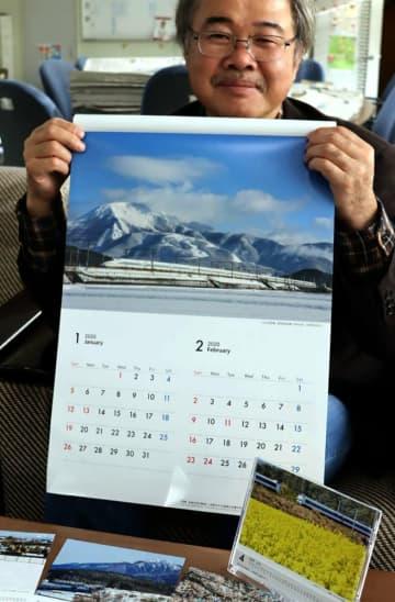 自作の鉄道カレンダーを手にする清水さん(滋賀県草津市役所)