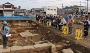 県埋蔵文化財センター職員(左)から説明を受ける参加者ら=佐世保市、早岐瀬戸遺跡