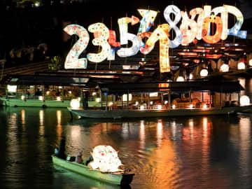 今年のえとのイノシシをかたどったあんどんを先頭に川へ繰り出す「こよみのよぶね」=22日午後5時44分、岐阜市、長良川