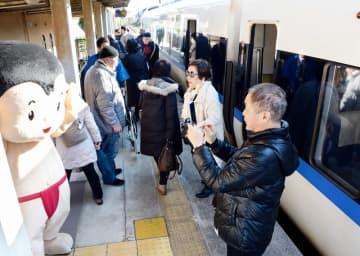 JR小浜線の若狭和田駅のホームに降りる京阪神の乗客。出迎えた赤ふん坊やとの記念撮影を楽しんだ=12月21日、福井県高浜町