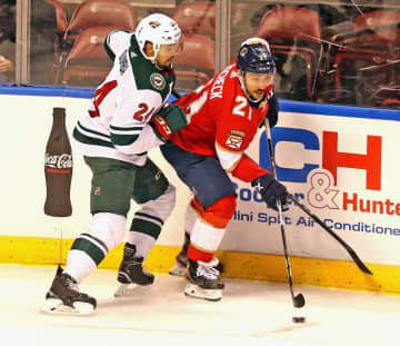 Florida Panthers' Vincent Trocheck (21) and Minnesota Wild's Matt Dumba (24) in the first period on Tuesday, Dec. 3, 2019 at the BB&T; Center in Sunrise, Fla. - CHARLES TRAINOR JR/Miami Herald/TNS