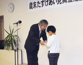 長谷川会長から見舞金を受け取る児童