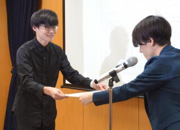 賞状を受け取る岡本太玖斗さん(左)=内閣府
