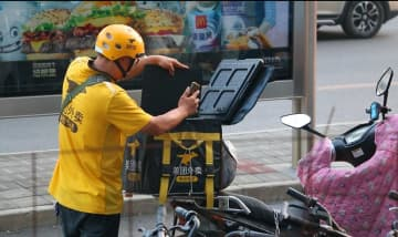 A Meituan food delivery driver picks up an order on Oct. 19, 2019 in Beijing. (Image credit: TechNode/Coco Gao)