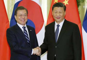 握手する中国の習近平国家主席(右)と韓国の文在寅大統領=23日、北京(聯合=共同)