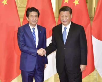 会談を前に握手する安倍首相と中国の習近平国家主席=23日、北京の人民大会堂(共同)