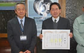 竹田副町長から贈られた感謝状を手にする幌村代表取締役(右)