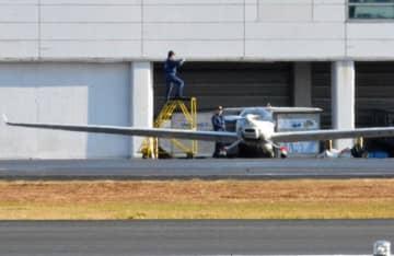 緊急着陸したモーターグライダーを調査する運輸安全委の航空事故調査官=23日午前、松山市南吉田町