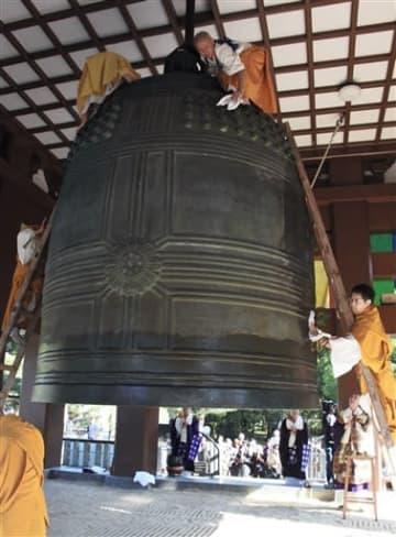 蓮華院誕生寺奥之院の大梵鐘を丁寧に拭き上げる僧侶ら=玉名市