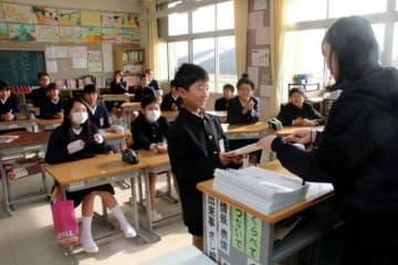 終業式の後、担任から通知表を受け取る開成小の6年生