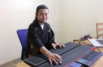 """最先端キーボードを操作し「ぜひ演奏を生で聞いて、""""見て""""ほしい」と話す薮井さん"""