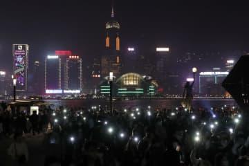 明かりのついたスマートフォンを掲げる抗議デモの参加者たち=24日、香港(AP=共同)