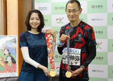 京くみひもと京友禅のメダルリボンを披露する山中教授(右)と中村さん=京都市中京区・市役所