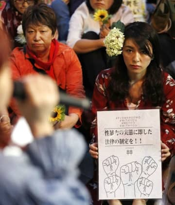 JR東京駅近くで開かれた「フラワーデモ」。抗議のメッセージを掲げる=6月11日夜